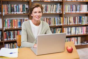 lachende leraar met behulp van laptop aan een bureau foto