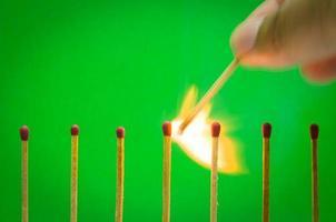 Burnning match setting op groene achtergrond voor ideeën en inspiratie foto