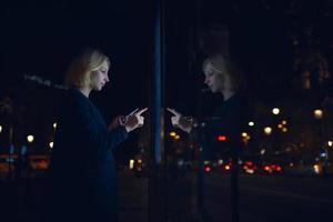 jonge vrouwen die moderne technologie in openlucht gebruiken
