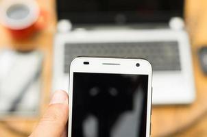 hand met slimme telefoon dicht bij camera en laptop wazig foto