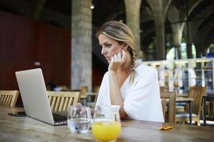 aantrekkelijke vrouwelijke freelancer die netbook gebruikt voor afstandswerk foto