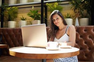 vrouwelijke freelancer die op laptopcomputer werkt tijdens het ontbijt in het café foto