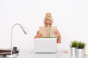 gelukkig blond meisje op haar werkruimte. vooraanzicht foto