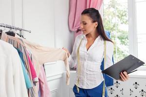 vrolijke jonge kledingontwerper controleert haar collectie foto