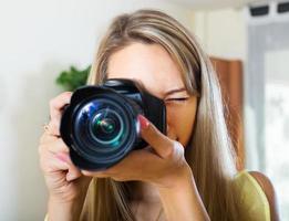 jong meisje dat met fotocamera werkt foto