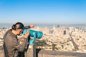 man kijken naar francisco downtown op een verrekijker van twin peaks foto