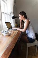 jonge brunette die bij haar huis aan laptop werkt. foto