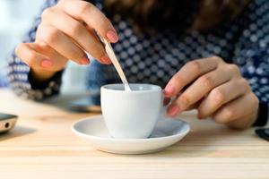 mooie jonge vrouw koffie drinken in haar kantoor. foto