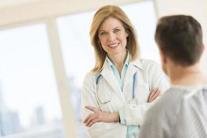 glimlachende vrouwelijke arts met patiënt in het ziekenhuis foto