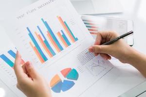 close-up van bedrijfspersoon die digitale tablet met financieel gebruikt foto