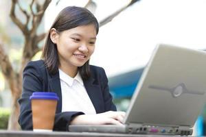 jonge vrouwelijke Aziatische zakenman met behulp van laptop
