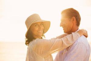 volwassen paar verliefd op het strand bij zonsondergang foto