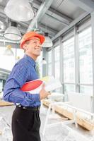vrolijke volwassen mannelijke ingenieur met schetsen van het gebouw foto
