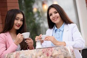 twee Aziatische zakenvrouw in brasserie en camera kijken foto