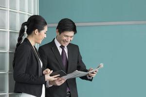 Aziatische zakenmensen lezen van elektronische tablet en krant. foto