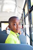 jonge jongen op een schoolbus foto