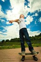 skater jongenskind met zijn skateboard. buiten activiteit. foto