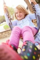 jong meisje spelen op schommel in de speeltuin foto