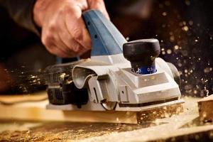 oudere man schaven van een plank van hout foto