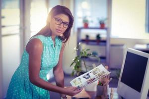gelukkige fotoredacteur die bij camera glimlacht foto