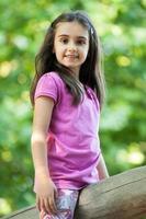 schattig klein meisje dat zich uitstrekt over een houten paal
