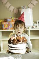 klein meisje blaast kaarsen foto