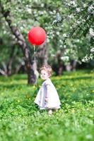 grappige babymeisje spelen met een grote rode ballon foto