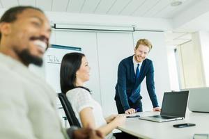 jonge mensen uit het bedrijfsleven zitten aan een conferentietafel