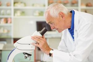 senior wetenschapper op zoek door microscoop