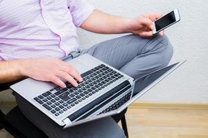 gebruik makend van. drukke man aan het werk met de computer en het gebruik van mobiele telefoon foto