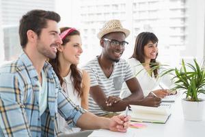 glimlachend teamwerk zitten en aantekeningen maken