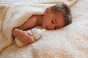 slapende baby met fles foto