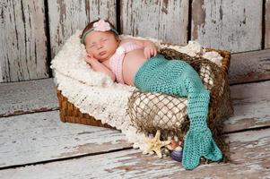 pasgeboren babymeisje in een zeemeermin kostuum foto