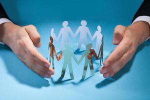 zakenman handen bescherming team van papier mensen op het bureau foto