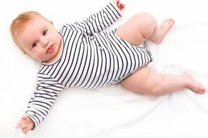 glimlachende babymeisje liggen in het bed foto