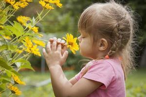 driejarig meisje snuiven gele bloem foto