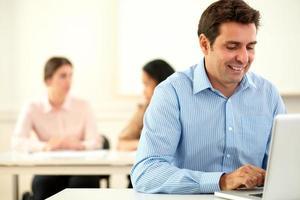 charmante man aan het werk op zijn laptop zittend foto