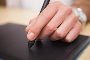 mannenhand puttend uit grafisch tablet