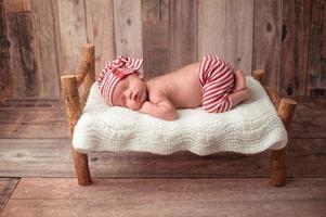 babyjongen slapen op een klein bed foto