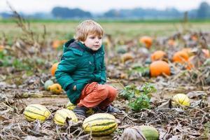 peuter jongen plezier zittend op enorme halloween pompoen foto