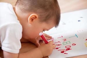 kleine jongen die zijn eerste brieven schrijft foto