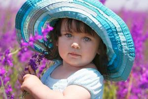 schattig meisje in grote blauwe hoed op natuurlijke achtergrond foto