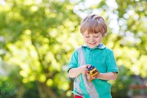 kleine peuter jongen speelt met auto speelgoed foto