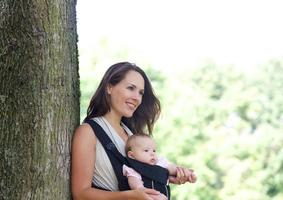 moeder lachend met baby in draagzak foto