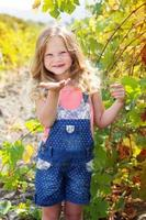 kind meisje stuurt klap kus in druiventuin foto