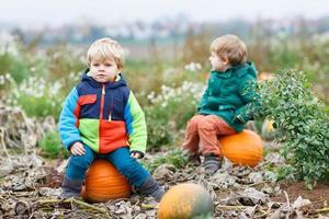 twee kleine broers en zussen zittend op grote pompoen foto