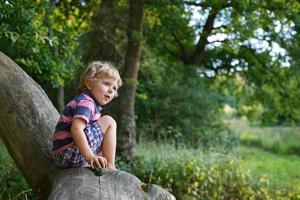 kleine schattige peuter jongen plezier op boom in het bos foto