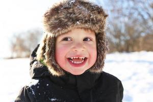 portret van glimlachende peuter die in de winter in openlucht loopt