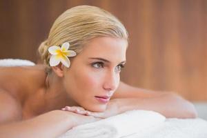 mooie vrouw liggend op een massagetafel in het spa center foto