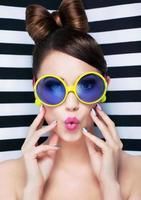 aantrekkelijke verraste jonge vrouw die zonnebril op gestreepte achtergrond draagt foto